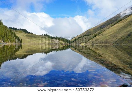 Delightful reflexion of the blue sky in water. Kel-Kogor, mountain lake
