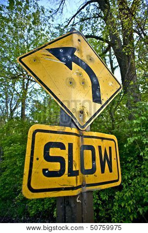 Bullet Holes Slow Down Sign