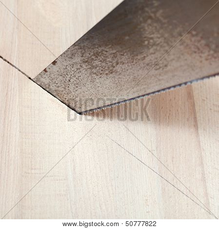 Wooden Board Is Cut With Hacksaw