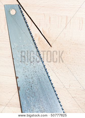 Hacksaw At Wooden Board