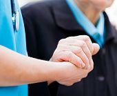 Caring nurse or doctor holding elderly lady's hand with care. poster