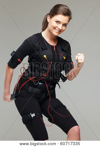 Young woman doing exercise  in Electro Muscular Stimulation EMS training costume  poster