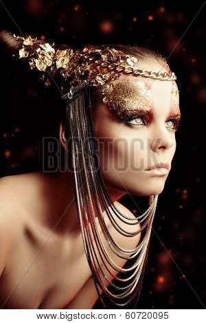 Art project: beautiful woman with golden make-up. Jewelry, make-up. Fashion.