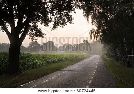 Country Road With Farm At Sunrise