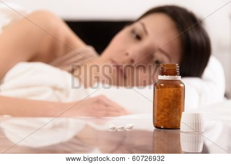 Woman In Bed Eyeing A Bottle Of Medication