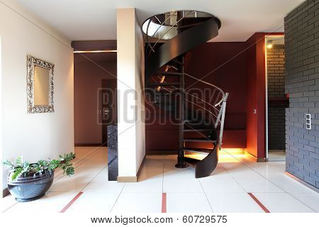 A modern staircase in a luxurious hall with a brickwall poster