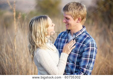 Young Caucasian Couple Standing In Tall Grass