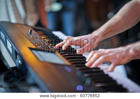 Closeup shot of male hands playing the piano. Human hands playing the piano on the party