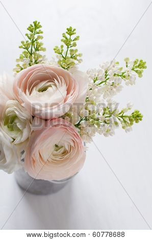Little delicate elegant bouquet of flowers buttercups and white lilacs in tin can on white wooden table poster