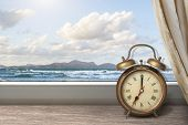 View of summer sea under blue sky from window with alarm clock poster