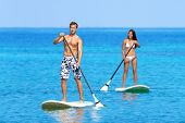 Paddleboard beach people on stand up paddle board surfboard surfing in ocean sea on Big Island, Hawaii Beautiful young multi-ethnic couple, mixed race Asian woman and Caucasian man doing water sport. poster
