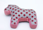 Gray and red textile toy horse with stars and stripes on white background poster