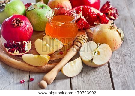 Pomegranate apple and honey traditional food of jewish New Year celebration Rosh Hashana. Selective focus. poster