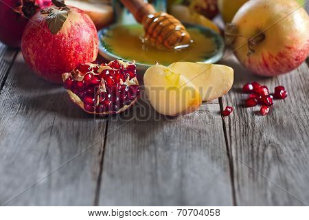 Pomegranate apple and honey traditional food of jewish New Year celebration Rosh Hashana. Selective focus. Copyspace background poster