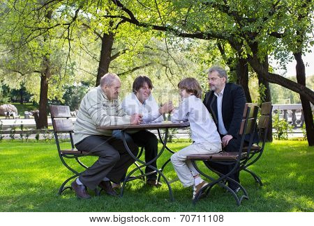 Great-grandfather, Grandfather, Father And Son Wrestling At A Wooden Table In A Park