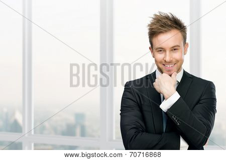 Half-length portrait of smiling manager touching face against window with urban view. Concept of leadership and success