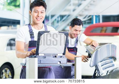 Asian Chinese car mechanics checking auto engine with diagnostics tool in his workshop poster