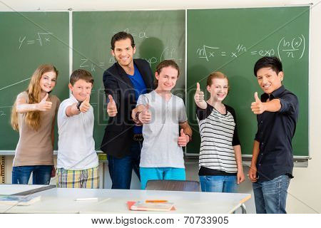 School and education - Teacher and students stand in front of a blackboard with math work in a classroom or class
