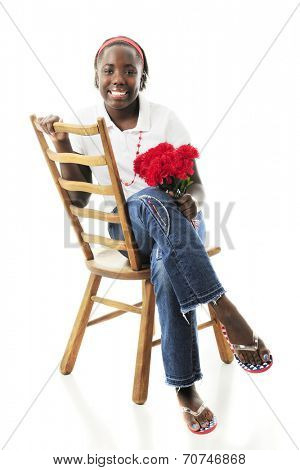 A happy preteen girl sitting pretty in an old ladder-back chair with a small bouquet of red flowers.  On a white background. poster