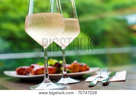 Table setting with two glasses of delicious white wine with chicken snack on background. Summer close-up. poster