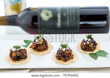 Micro Bruschetta of Chocolate Eggplant Caponata with Chocolate Balsamic Vinegar & Crumbled Haystack Mountain Goat Cheese appetizers. poster