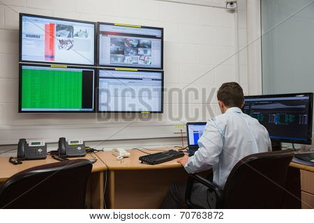 Technician sitting in office running diagnostics in large data center poster