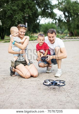 Young family with two boys playing with RC toy