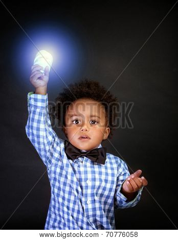 Portrait of a cute little schoolboy holding in hands bright lamp, smart boy learning science