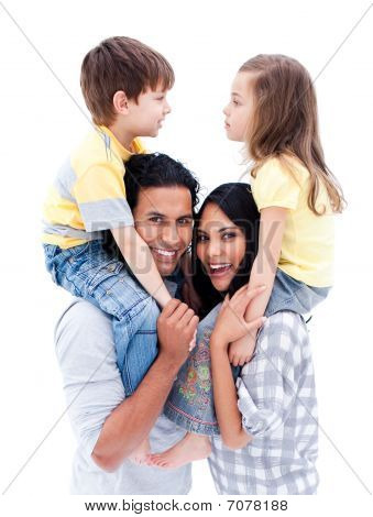 Smiling Parents Giving Piggyback Ride To Their Children