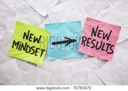 new mindset and new results  concept - colorful sticky notes on a background of crumpled white notes