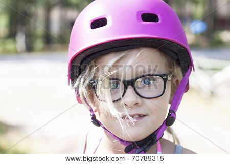 Child With Pink Bicycle Helmet And Black Glasses