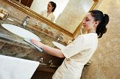 Hotel service. female housekeeping worker cleaning table from dust in bathroom poster