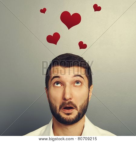 concept photo of man in love. amazed young man looking up at red hearts over grey background