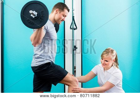 Patient at the physiotherapy doing physical exercises using bar bell