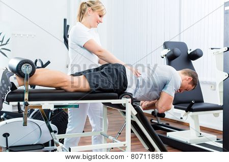 Patient at the physiotherapy doing physical exercises with therapist with sport doctor poster