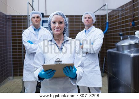 Girl holding a clipboard with these colleagues behind her in the factory