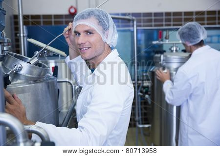 Portrait of a smiling scientist working with brewer in the factory