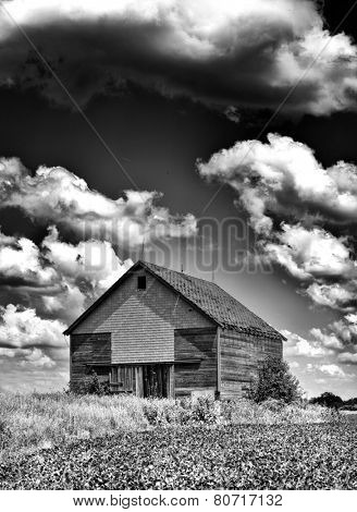 Spooky old desolate haunted barn with storm clouds overhead like you would see on Halloween in Black and White