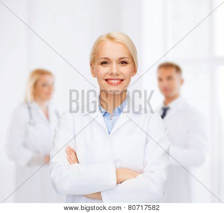 healthcare and medicine concept - smiling female doctor over group of medics in hospital poster