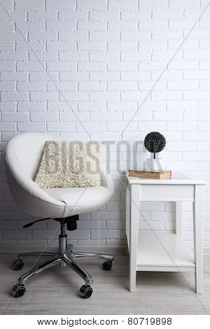 Modern interior with chair and pillow on it on white brick wall background