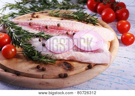Pangasius fillet with herb, spices and vegetables on cutting board and color wooden table background poster