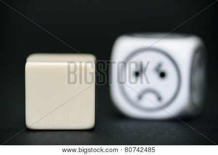 Blank Dice With Emoticon Dice (sad) In Background