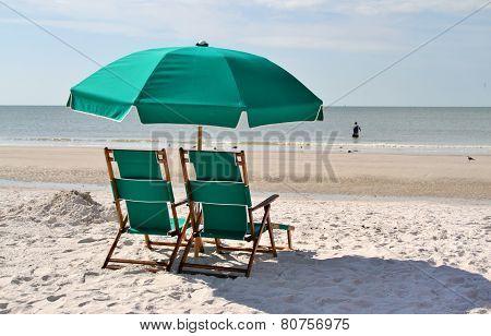 Green sun chairs and umbrella