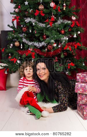 Cheerful Mother And Son Under Christmas Tree