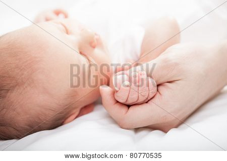 Newborn baby holding mother's thumb