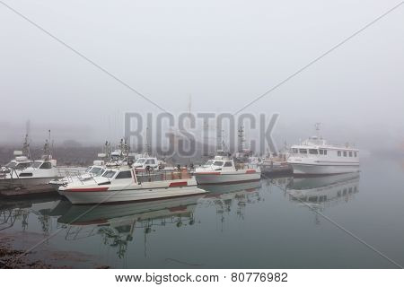 Fishing vessel in a foggy misty morning at Harbor in Hofn Iceland poster