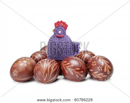 Crochet sitter sitting on pile of easter eggs shot on white