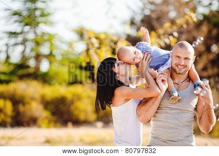 Young happy family on a walk in the park in the summer.