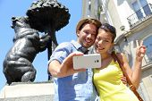Tourists taking selfie photo pictures by famous bear statue Madrid on Puerta del Sol. Young couple using smartphone camera at tourist attraction Bear and the Madrono Tree, symbol of Madrid, Spain. poster