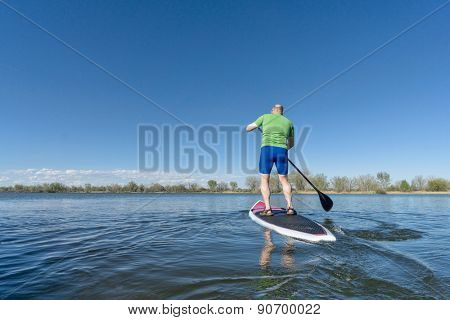 senior male on SUP (stand up paddleboard) on a lake under Colorado blue sky